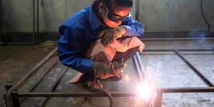 A woman is seen welding steel in Nepal