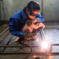 A woman is seen welding steel in Nepal